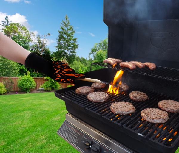 Cooking with BBQ glove with burgers and flames