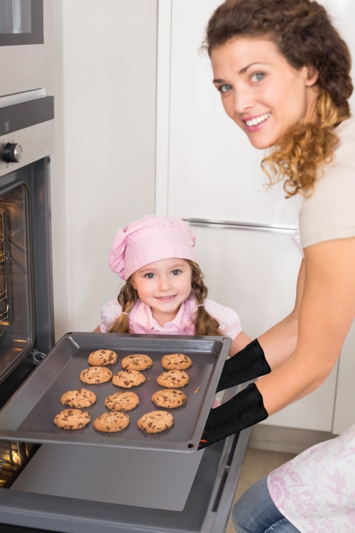 woman removing cookies from oven while girl looks on