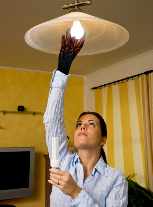 Woman reaching to change hot light bulb while wearing black gloves